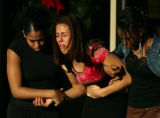 Mourners (from left) Sheila Olaechea, cq, 17, a junior at Grand View, Sara Nehf, cq, 16, a junior...