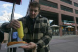 Jim Blackstone (cq) puts some mustard on his hot dog from pushcart vendor Valentina Petty (cq)...