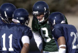 Quarterback John Dutton (8) calls the play in the huddle with Toure Carter (11) and Herman Bell...