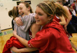 Regis High School Kaily Baneati,, 16, (sophomore team) left, hugs teammate Taylor Johnson, center,...