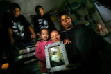 Margarita Guzman, 49, holds a photograph of her murdered son Edgar Chacoy and her daughter...