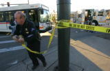 Denver Police officer Dan Cameron ropes off the scene of a fatal RTD bus verses pedestrian...