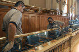 Joe Jiron (cq) and Rita Carter (cq) clean the glass and   brass railing on the third floor of the...