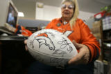 Ellen Levine-Jones (cq), 64, of Commerce City shows off a football signed by numerous current and...