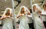 Bride-to-be Laura Sandhoff (cq), 26, of Littleton, looks in a trio of mirrors as she tries on a...