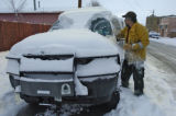 Pat McLaudhlin (cq), Forest Service out of Golden, clears snow off his truck in Aguilar Monday...