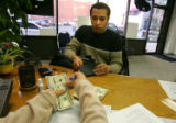The hands of Paycheck Loans manager Nicole Ramirez counts out the remainder of a $200 loan that...