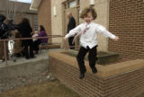 Ammon Boyce,5, jumps off the ledge keeping himself occupied as his mom, Sharon holding Gracelynn,...