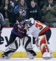 Colorado Avalanche goaltender David Aebischer, left, gets tangled up with Calgary Flames...