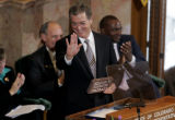 Colorado Governor Bill Owens holds up a miniature version of the signs that welcome people to the...
