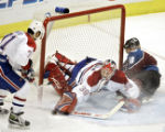 The Colorado Avalanche's Alex Tanguay (#18) crashes into Montreal Canadiens' goaltender Cristobal...