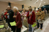 The crowd stands for the Pledge of Allegiance at the Willie Estrada Civic Center in Alamogordo,...