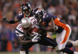 Patriots wide receiver Deion Branch covers up while being dragged down by Broncos safety Nick...