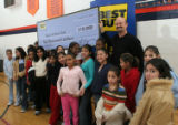 Best Buy district manager Jeff Fogelman presents a check for $10,000 to a group of kids, Monday,...