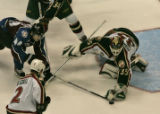 In the first period, Wild's Manny Fernandez (release) puts puck and stick at hand to stop Avs'...