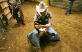 Steven Anding, of Crossroads, TX, tapes up his arm and stretches before the bareback bronc riding...