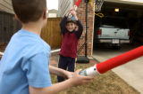 Cameron Davis, left, 7, and friend Jack Lang, 6, play with light-sabers outside the Lang home in...
