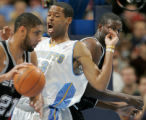 Denver Nuggets' center Marcus Camby, middle, draws a offensive foul on San Antonio's Tim Duncan,...