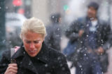 Rachel Svenson (cq), of Denver, braces herself against the wind and snow, as she crosses the...