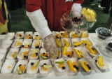 Brett Carlsen (cq), of Obim Fresh Cut Fruit, fills trays with fruit Thursday afternoon March 23,...