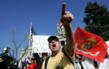 Timothy Coon (cq), of Denver, center, yells at members of the Westboro Baptist Church, after being...