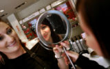 Kristen Carsrud (cq, right and reflected in mirror), 19, of San Francisco, Ca. flashes a smile at...