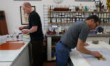 Printing assistant Evan Colbert of Longmont and master printer Bud Shark ready the paint and press...