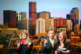 With a backdrop of the skyline of Denver behind them Wheel of Fortune host Pat Sajak (center)...