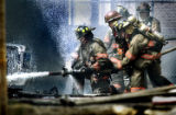 (DENVER, Colo., May 9, 2004) Denver firefighters spray foam as they battle a fire in an alley in...
