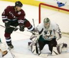 Andrew Brunette jumps up in front of the goal as a shot hits goalie Jean-Sebastien Giguere in the...
