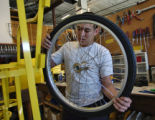 Ian Anderson (cq) puts a wheel on a frame of a Board Walker, different type of Pedicab,Tuesday...