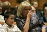Monica Goetsch (cq) wipes tears from her eyes as Susan Moran  (cq) , widow of murdered Denver...