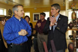 Bill Ritter, left, listens while Congressman Mark Udall, right, and others applaud Udall's...