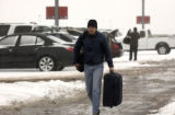 Steve Chappell, cq, of Boulder carries his luggage through the parking lot at Denver International...