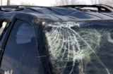 A smashed windshield and roof show the magnitude of a accident as wrecked van sits in a lot at...