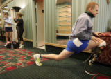 Major Dave Rozelle, who lost part of his leg in an explosion in Iraq, stretches before running a...