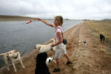Jill Brenn, cq, owner of Adventure Hounds, throws a toy in to the water at a private lake in...