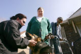 Denver police officer Samantha McPherren (cq), left, pets Vida, center, a seeing eye dog for Lee...