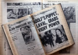 Archived copies of the Rocky Mountain News in broadsheet and tabloid formats lay open on a table...