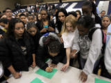 William C. Hinkley High School students sign a petition following a voluntary school assembly...