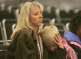 Kirstin Smith, left, comforts her son Alec Smith, 9, after he was the first of her three sons to...