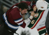 Colorado Avalanche player Bob Boughner, left, and Minnesota Wild player Alex Henry go to blows in...