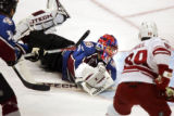 The Colorado Avalanche's Jose Theodore (#60) dives for a loose puck as the Phoenix Coyotes' Mike...