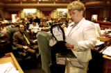 Rep. Debbie Benefield D-Arvada, reads the back of her cardboard doll Tuesday, March 28, Colorado...