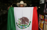 Jesus Contreras, 78, holds the largest of the Mexican flags sold in his nieces store Discos Aguila...