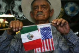 Jesus Contreras, 78, holds a couple Mexican and United States, which are sold in his nieces store...