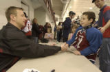 Rob Blake, (cq), shakes hands with Aaron Lee,(cq), 9, as his sister Annika, (cq), 7, pink dress...