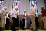 Parishioners celebrate communion on Holy Thursday in the Chapel at the Little Sisters of The Poor...