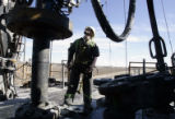 Derick man Jason Rangel (cq) works on the Ensign Rig 1 east of Eaton Thursday , March 30, 2006. An...