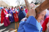 Enrique Casillas (cq), of Denver, carries the cross as he plays Simon of Cyrene, as about 40...